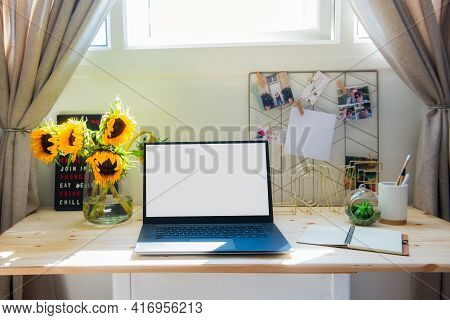 Home Office Workspace. Wooden Desk With Laptop Mockup White Empty Screen, Mood Board With Pined Note