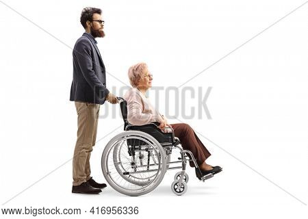 Full length profile shot of a bearded man pushing an elderly lady seated in a wheelchair isolated on white background