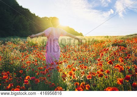 Backview Happy Young Woman In A Pink Dress With Raised Arms Relaxing In Red Poppies Flowers Meadow I