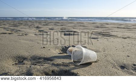 Disposable Plastic Glass Discarded On Sea Coast Ecosystem, Nature Waste Pollution