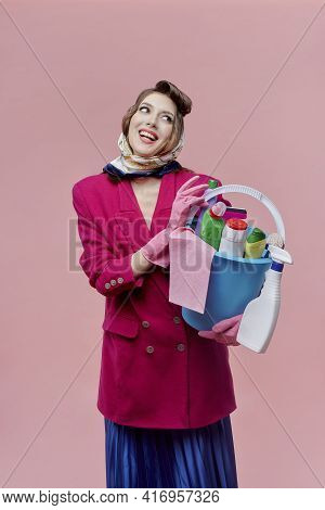 A Stylish Happy Woman Holds A Bucket Of Cleaning Tools. Bright Makeup.