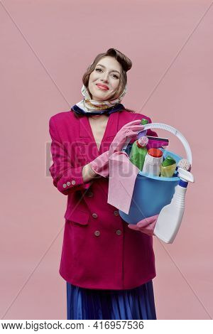A Female Housewife Holds A Bucket Of Cleaning Tools. Routine Work. Bright Makeup