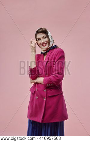 A Brunette Woman With Very Bright Makeup In A Pink Jacket And A Long Blue Skirt.