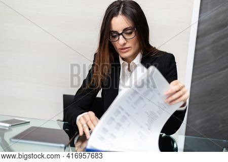 Close up of woman hands doing paperwork at glass desk. Secretary concept