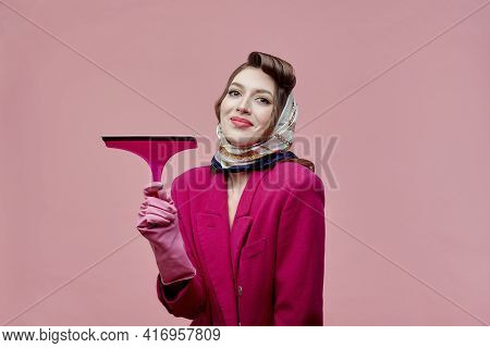 A Young Woman Wearing Rubber Gloves Holds A Window Cleaning Tool. Bright Makeup.
