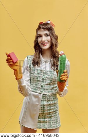 A Cleaning Woman Holds A Bottle Of Household Chemicals And A Sponge.