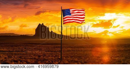 American National Flag Composite In Dry Desert With A Mountain Peak In The Background. Colorful Suns