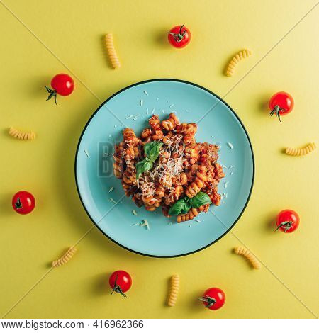 Creative Composition With Pasta, Tomato Sauce, Cheese And Basil On A Yellow Background. Minimal Flat