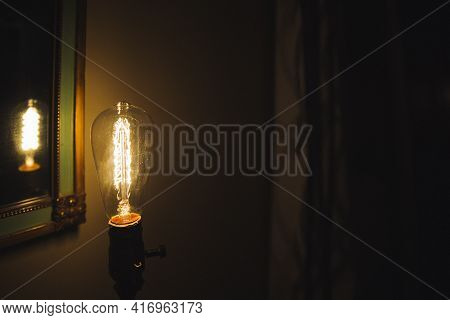 Incandescent Bulb. Vintage Hanging Edison Light Bulb In A Dark, Spooky Room With Curtains