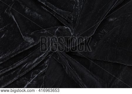 Colored Black Textile Satin Fabric Folded In Folds And Waves With Highlights And Texture Shimmers In
