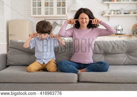 Frowning Mom And Son Sit On Couch With Closed Eyes And Cover Ears From Noisy Music Or Fight Sounds F