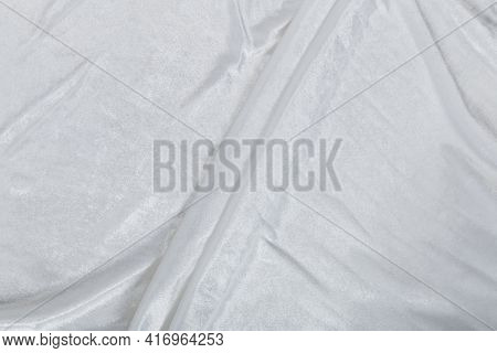 Colored White Textile Satin Fabric Folded In Folds And Waves With Highlights And Texture Shimmers In
