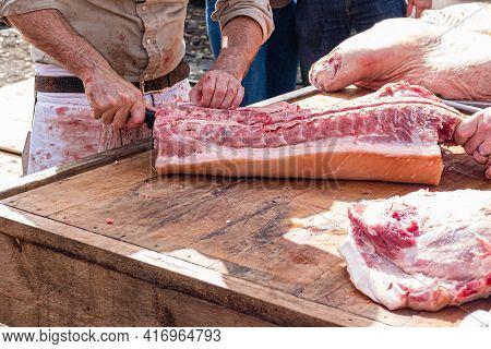 Man Butchering Pork Ribs At A Cajun Boucherie