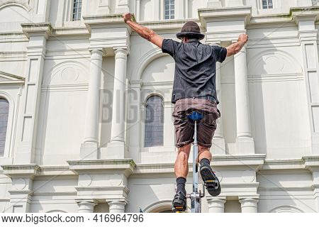 New Orleans, La - February 11: Street Performer Poses Triumphantly On Tall Unicycle In Front Of St.