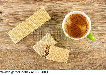 Whole Wafer With Chocolate Filling, Halves Of Wafer, Coffee Espresso In Green Cup On Brown Wooden Ta