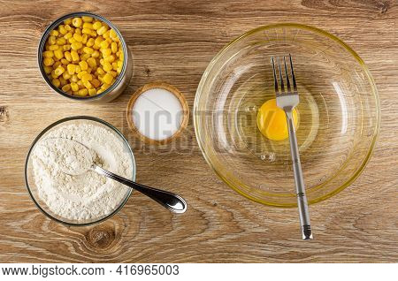 Cooking Corn Pancakes. Jar Of Sweet Corn, Spoon In Bowl With Flour, Salt In Bamboo Bowl, Fork In Tra