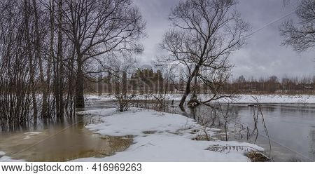 Melted Snow In The Foreground. Early Spring. The River Is Overflowing. Dry Grass Is Visible From Und