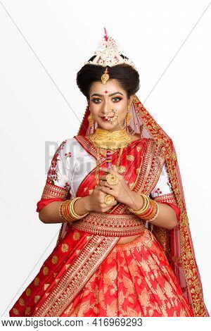 Stunning Indian Bride Dressed In Red Traditional Banarasi Sari Embroidered With Gold Jewellery And B
