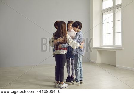 Small Group Of School Children Huddling Standing In Circle In Spacious Empty Room