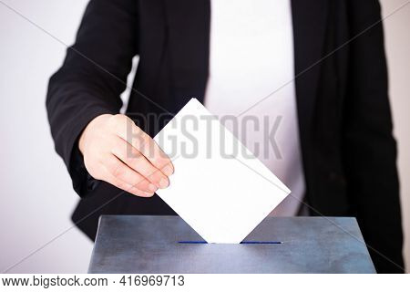 Hand of a voter putting vote in the ballot box. Election concept.