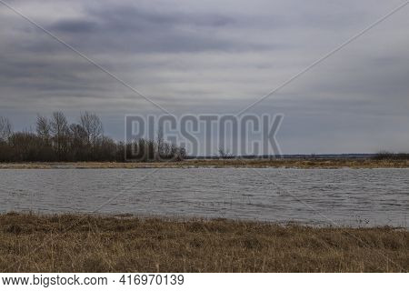 Landscape With A Flooded Field. On A Cloudy Day With A Grey Spring Sky. The River Is Overflowing. Dr