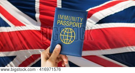 tourism, travel and health care concept - hand holding immunity passport over flag of great britain on background