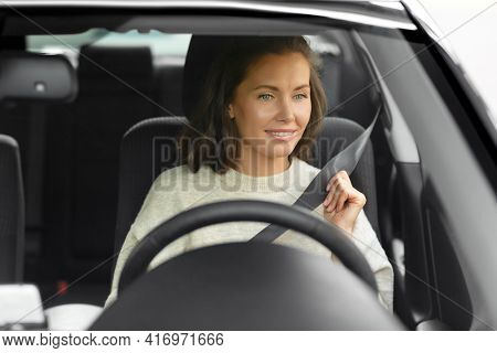 safety and people concept - happy smiling young woman or female car driver fastening seat belt