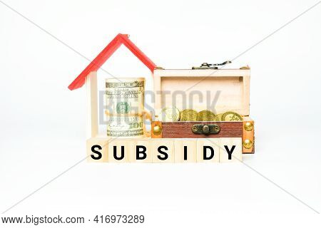 A Picture Of Wooden Block With Subsidy Word, House Miniature, Gold Chest And Fake Money Insight. Pro