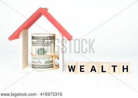 A Picture Of House Miniature And Fake Money With Wooden Block Written Wealth. Wealth Management Conc