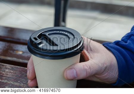 Close-up Of A Man's Hand With A Bamboo Coffee Cup With Lid. Man Holding A Brown Cup With A Black Lid