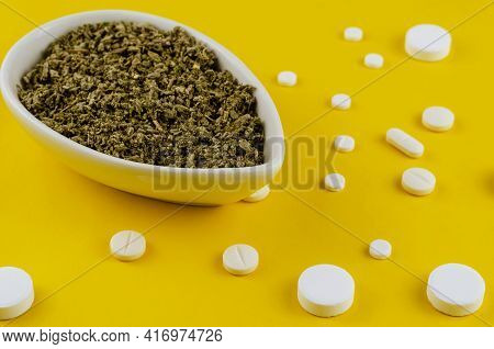 Mix Of Dried Medicinal Herbs In White Ceramic Bowl And Pills On Yellow Background. Crushed Medicinal