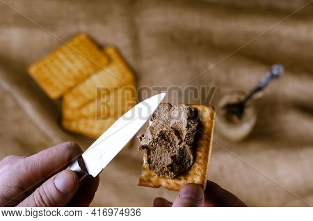 Close-up Of A Hand Spreading Pate On A Cracker With A Knife. A Man Prepares Himself An Appetizer Wit