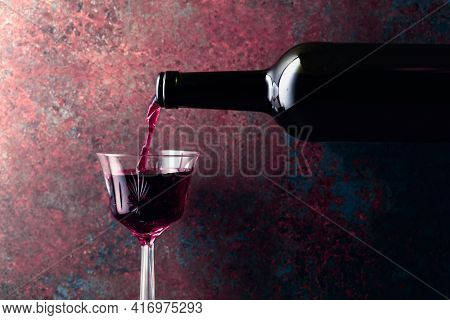 Port Wine Or Fortified Red Wine Is Poured From A Bottle Into A Glass On A Rusty Brown Background. Co