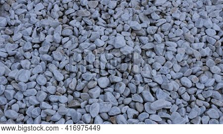 Top View Of A Gravel Smooth Embankment Of Solid Gray Stones, A Stony Light Background Of A Shallow D