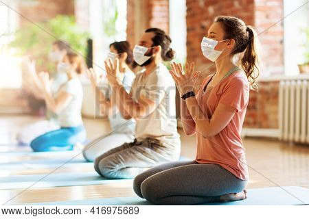 fitness, yoga and healthy lifestyle concept - group of people wearing face protective medical mask for protection from virus disease doing lotus seal gesture and meditating in seated pose at studio