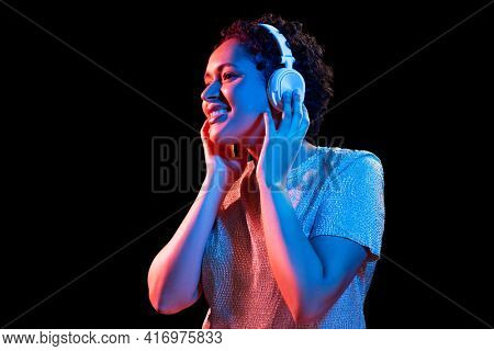 nightlife, technology and people concept - happy young african american woman in headphones listening to music in neon lights over black background
