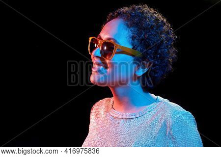 leisure, clubbing and nightlife concept - smiling young african american woman in sunglasses over ultraviolet neon lights on black background
