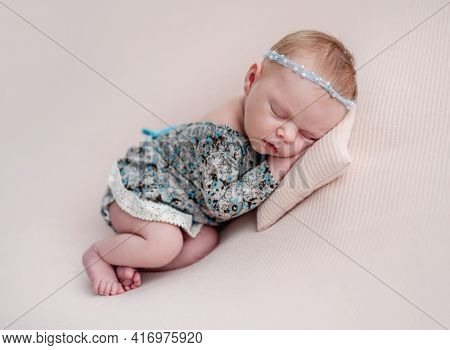 Newborn girl wearing diadem and dress resting on tiny pillow
