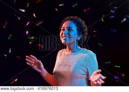 leisure, party and nightlife concept - happy smiling young african american woman under confetti over ultraviolet neon lights on black background