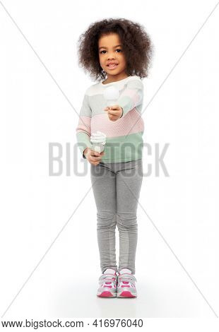 eco living and sustainability concept - smiling african american girl comparing energy saving light bulb with incandescent lamp over white background