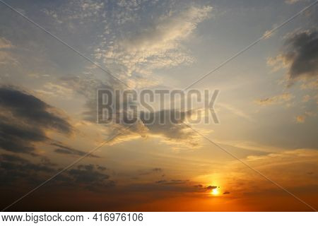 Sunset On Colorful Sky, Sun Is Shining Through The Dark And Orange Clouds. Picturesque Landscape For