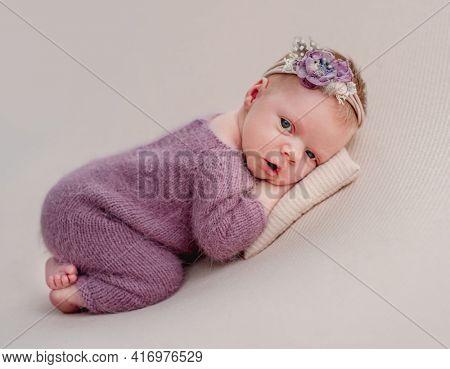 Awake newborn girl with flower diadem lying on tiny pillow
