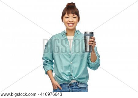 sustainability and people concept - portrait of happy smiling young asian woman in turquoise shirt with thermo cup or tumbler for hot drinks over white background