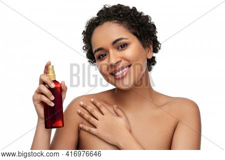beauty, sun protection and bodycare concept - portrait of happy smiling young african american woman sunscreen oil spray in bottle over white background