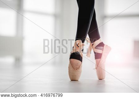 Closeup view on beautiful ballerina legs wearing black leggings and beige pointe shoes, staying on tiptoes during ballet dance class