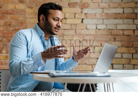 Middle eastern unshaven man gesturing while working with laptop in office