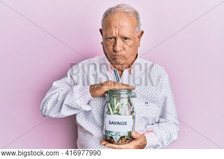 Senior caucasian man holding jar with savings skeptic and nervous, frowning upset because of problem. negative person.