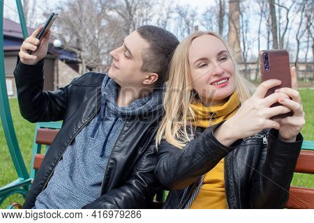 Husband And Wife Take A Selfie While Sitting On A Swing In The Park. Happy Couple Taking Pictures Of