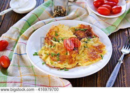 Potato Fritters On A White Plate On A Wooden Background. Jewish Food. Hanukkah Concept