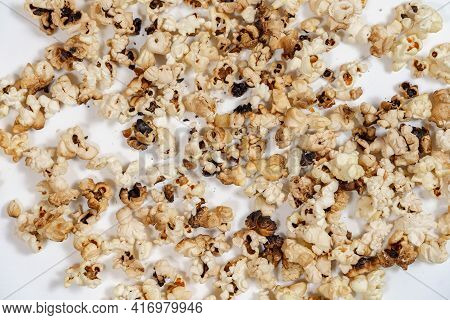 Spoiled Burnt Grains Of Popcorn Close-up. Popcorn, Overdone, Isolated